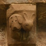 hound and hare corbel on the exterior apse wall
