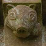 'Greasy' pig with man in its mouth on the  exterior north wall of the apse